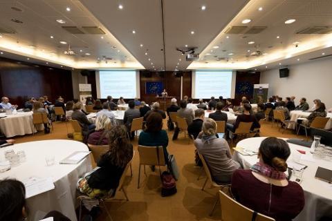 Foto toont de deelnemers aan de conferentie die een presentatie volgen